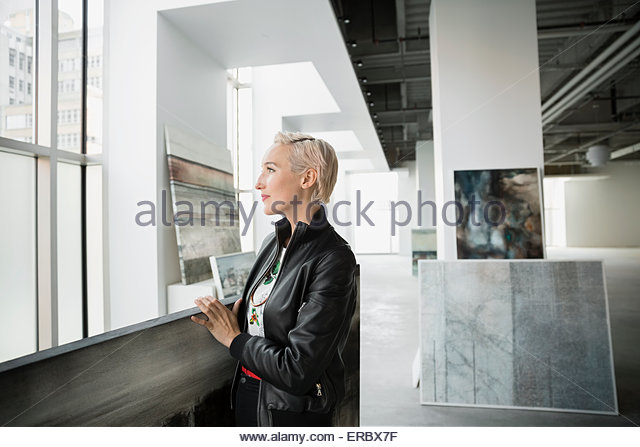 Smiling artist with paintings in art gallery - Stock-Bilder