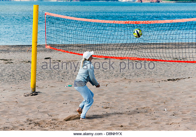 Young woman playing beach volleyball at Exmouth, Devon, UK. - Stock Image