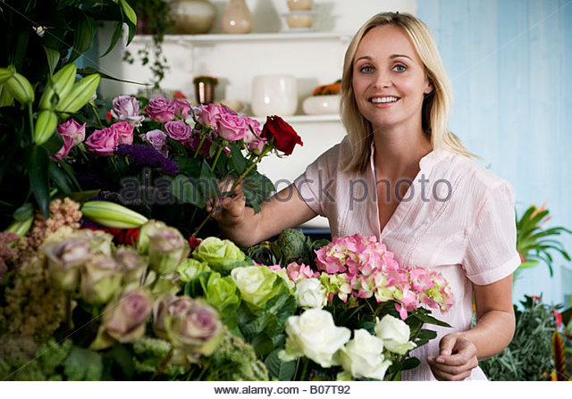 Woman florist in her shop, surrounded by an assortment of flowers - Stock Image