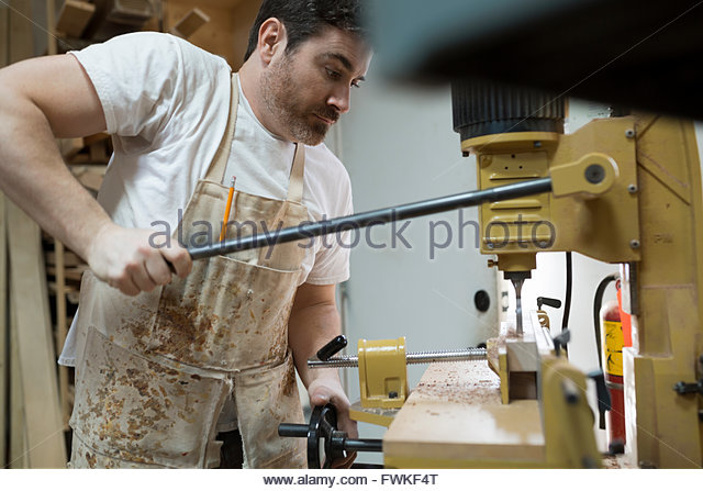 Carpenter using drill press in workshop - Stock Image