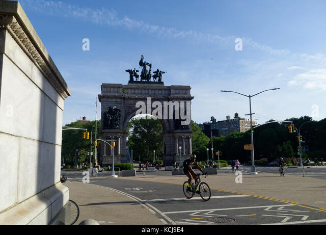 Pedestrians and cyclists at the Grand Army Plaza monument by Prospect Park. - Stock Image