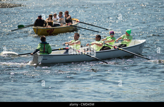 Crews from all over Wales competing in the celtic longboat rowing competition in the warm sunny weather at  Aberystwyth - Stock Image