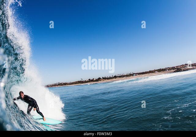 Close up of ocean wave and mid adult man surfing, Carlsbad, California, USA - Stock Image