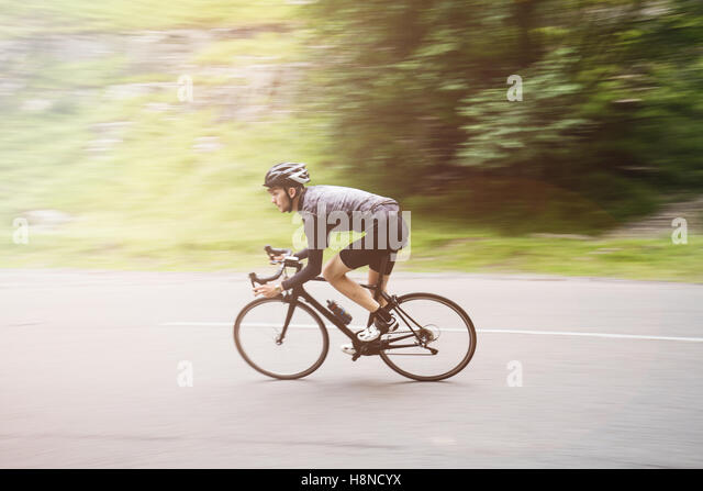 Panning shot of a young cyclist going round a corner in Cheddar George - Stock-Bilder