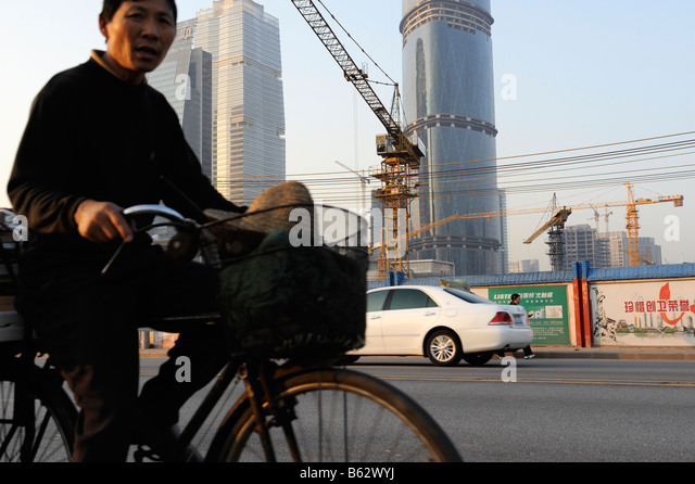 Chinese cyclist passes a construction site - Stock-Bilder