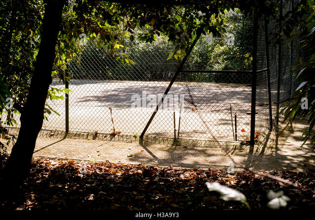 A hard tennis court bathed in morning sunlight - Stock Image