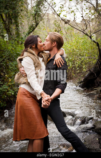 Woman and man kissing in the creek. - Stock Image