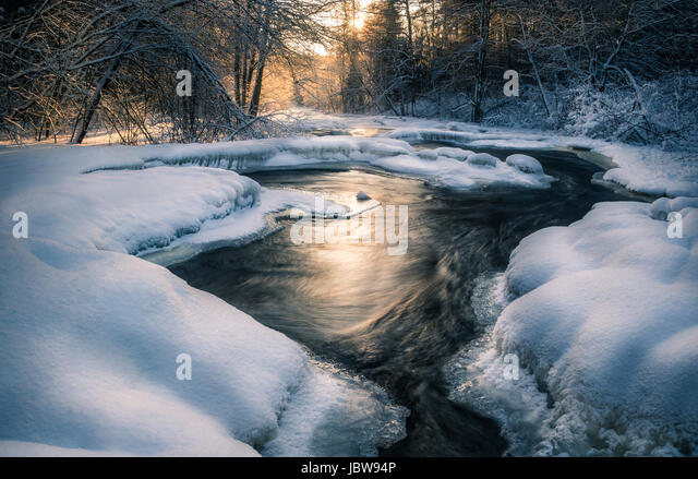 Scenic landscape with flowing river at winter morning - Stock Image
