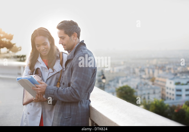 Business people talking at ledge overlooking Paris, France - Stock Image