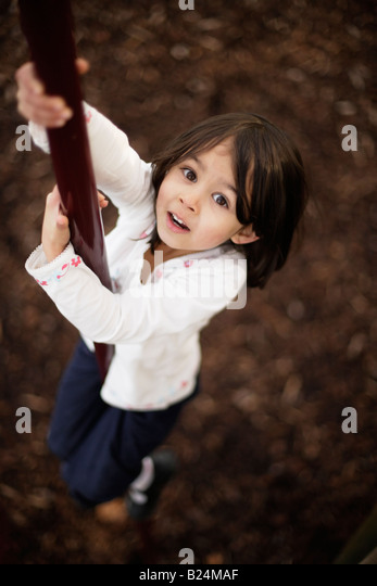 Girl aged five plays in adventure playground sliding down pole - Stock Image