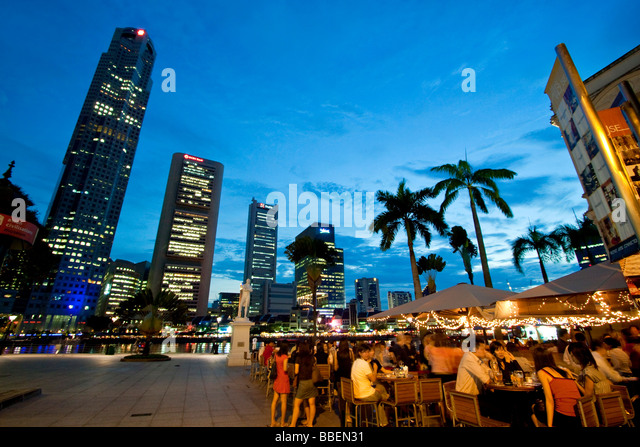 Skyline of Singapores Raffles Statue street cafe South East Asia twilight - Stock Image