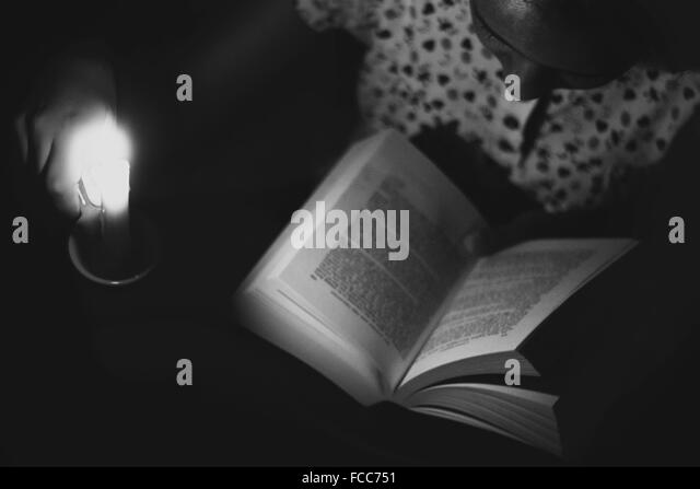 Close-Up High Angle View Of A Girl Reading Book In The Dark - Stock Image