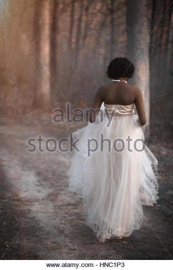 Elegant young woman in the woods walking away - Stock-Bilder