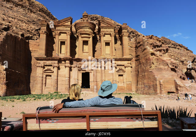 Tourist enjoying the view of The Monastery - one of Petra's prettiest Nabatean monument. - Stock Image