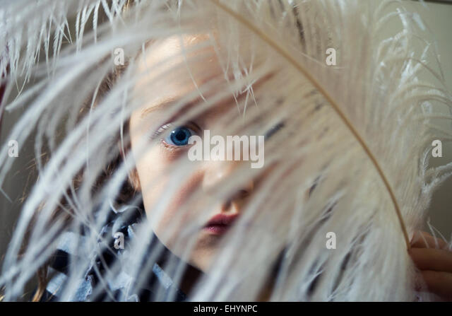 Girl with a feather in front of her face - Stock Image
