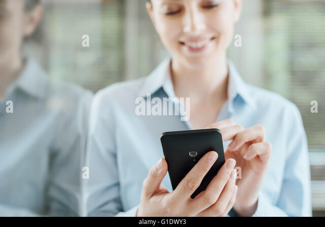 Beautiful smiling young woman using a smart phone, leaning on a window and reflecting on glass - Stock-Bilder