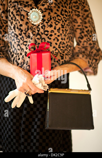 Portrait midsection of well-dressed woman with gloves, purse and leopard print coat holding wrapped gift - Stock Image