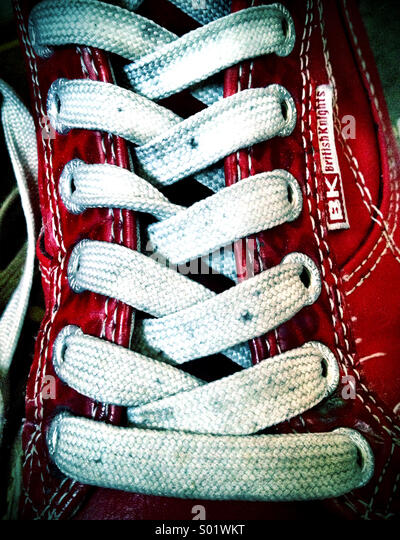 Close-up of laces on beat up red sneakers - Stock-Bilder