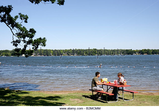 Wisconsin Kenosha Paddock Lake Old Settlers Park Asian man woman couple picnic bench lakeshore outdoor recreation - Stock Image