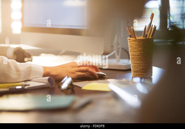 Businesswoman using computer and computer mouse at desk - Stock-Bilder