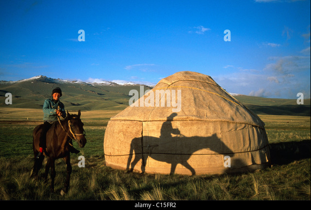 Horse and rider in front of a yurt, Moldo-Too Mountain Range, Song-Kul, Kyrgyzstan, Central Asia - Stock Image