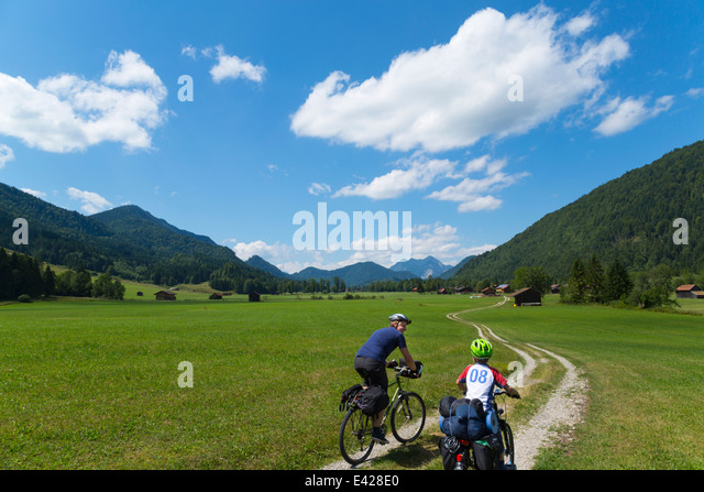 Father and son cycling through Jachenau, Bavaria, Germany - Stock Image