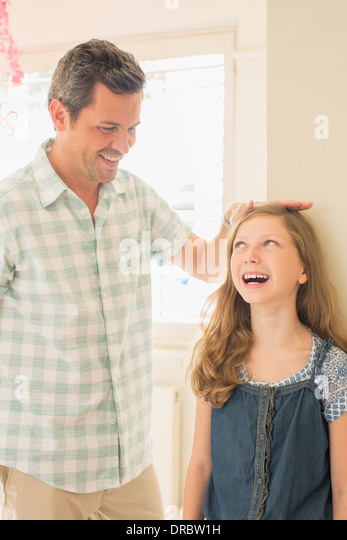 Father measuring daughter's height on wall - Stock Image