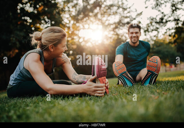 Fitness couple stretching outdoors in park. Young man and woman exercising together in morning. - Stock Image