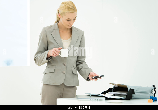 Professional woman holding coffee cup, looking down, text messaging - Stock-Bilder