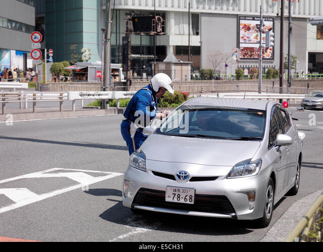 Police officer checking a drivers license of a driver in a stopped car. Tokyo, Japan. - Stock Image