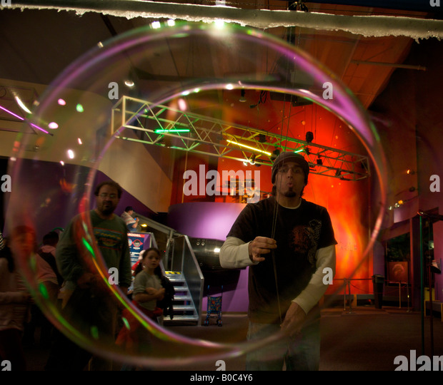 Man blowing a large soap bubble at the Pacific Science Center, Seattle, Washington, United States, North America. - Stock-Bilder