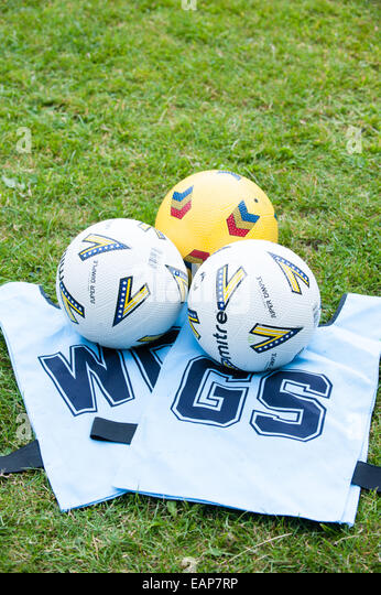 Clean white netball tabards and three netball balls on the grass at a school coaching course - Stock Image