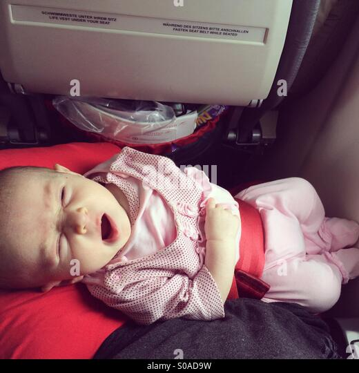 One month baby in plane yawning - Stock Image
