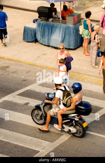 Grand Cayman George Town cayman islands tourists crowd motor scooter - Stock Image