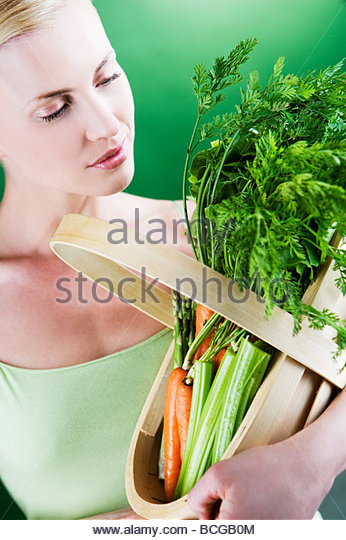 A young woman holding a basket full of vegetables - Stock Image