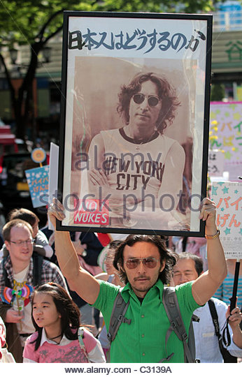 An activist holds up a picture of John Lennon during an anti-nuclear, pro renewable energy protest march in Shibuya, - Stock Image
