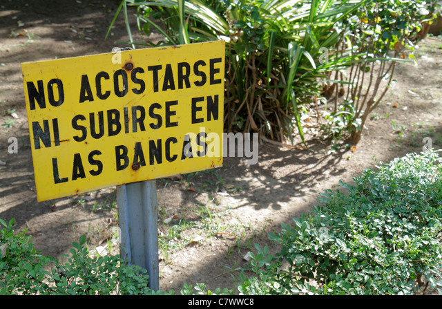 Managua Nicaragua Central Park sign Spanish language information warning prohibit no sleeping no climbing on benches - Stock Image