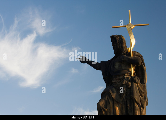 Statue on the Charles Bridge pointing at a cloud in Prague, Czech Republic. - Stock-Bilder