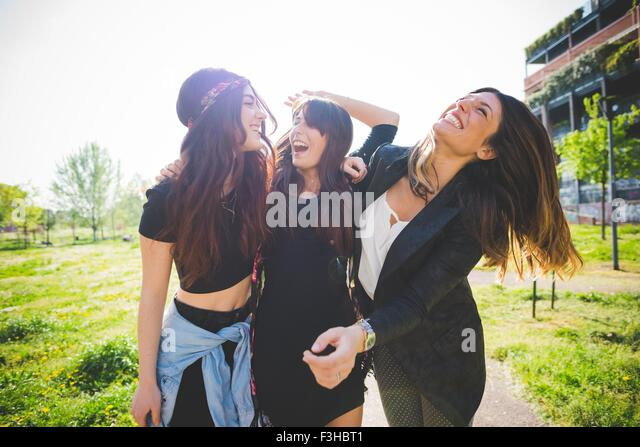Three young female friends laughing together in park - Stock Image