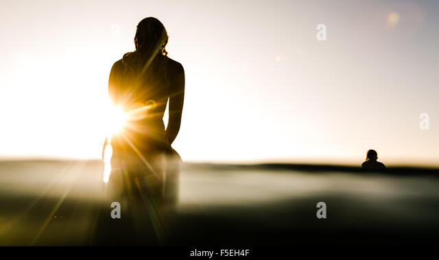 Silhouette of two surfers at sunrise - Stock Image