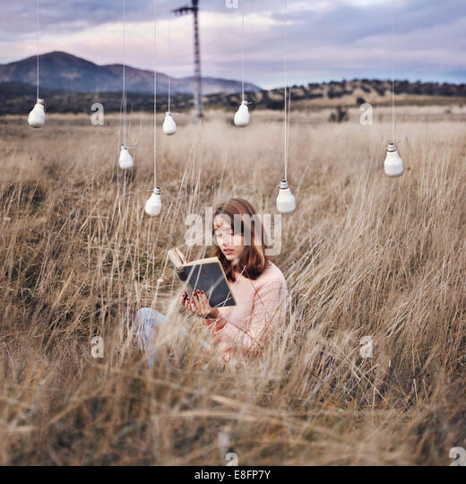 Woman reading book in field under low energy light bulbs suspended on wire - Stock Image