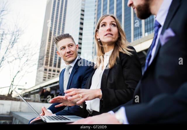 Businesswoman explaining colleagues using laptop while sitting against building - Stock-Bilder