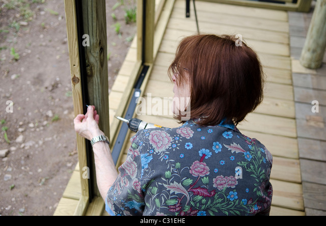 woman building screened porch - Stock Image