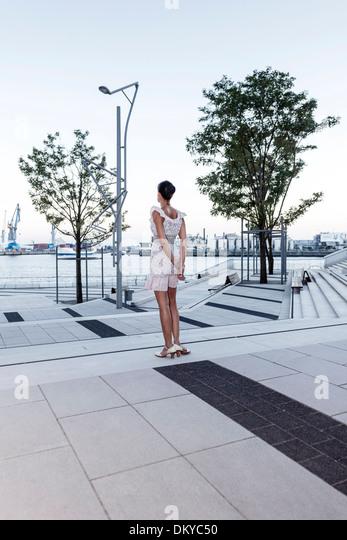 Young woman looking at river Elbe, HafenCity, Hamburg, Germany - Stock Image