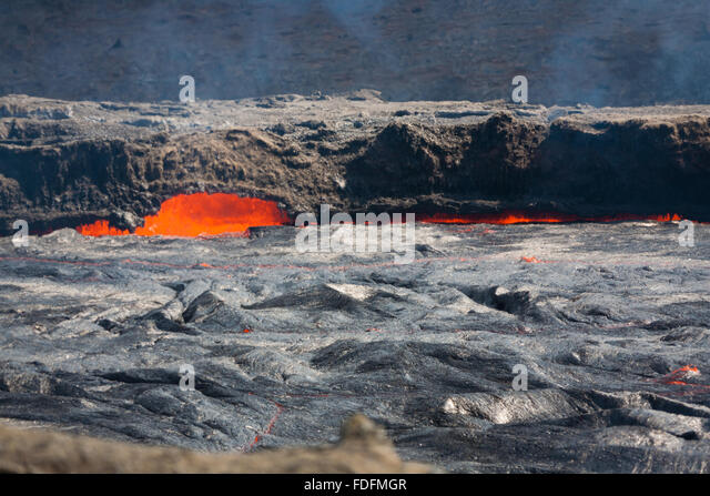 A thin crust of cooled lava moves slowly across the lava lake of Erta Ale volcano in Ethiopia. Molten rock splashes - Stock Image