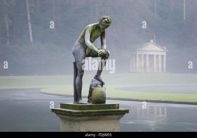 A misty, winter view of a statue in front of the Temple of Piety at Studley Royal Water Garden, North Yorkshire. - Stock-Bilder