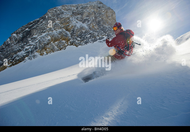A snowboarder smiles as he rides the powder in the backcountry of the Selkirk Mountains, Canada. (backlight) - Stock Image