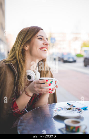 young beautiful blonde hipster woman at the cafe bar drinking from a cup of coffee - Stock Image