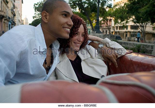 Young multi-ethnic couple car, Havana, Cuba - Stock Image
