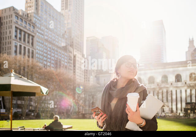 Businesswoman holding smart phone and laptop while waiting at Bryant Park - Stock-Bilder